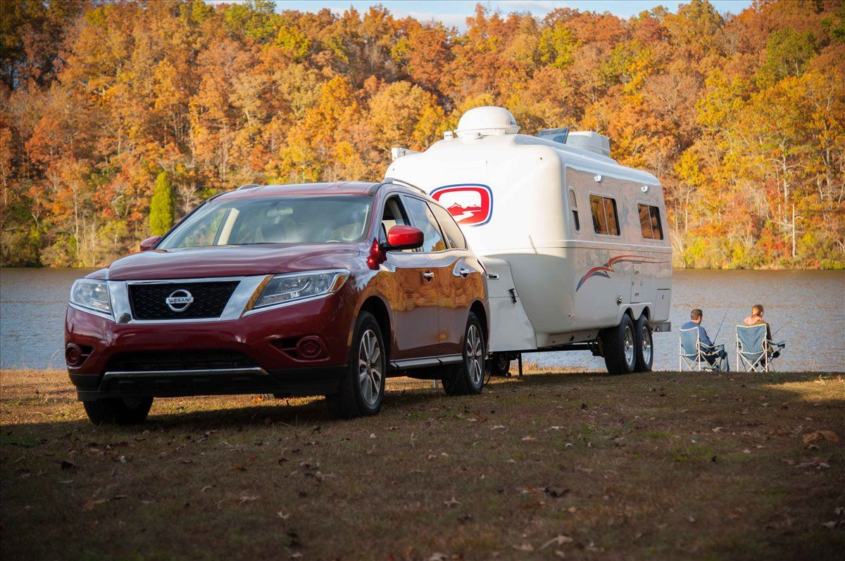 oliver travel trailers legacy elite 2 overview of lake and forests in the fall with couple fishing
