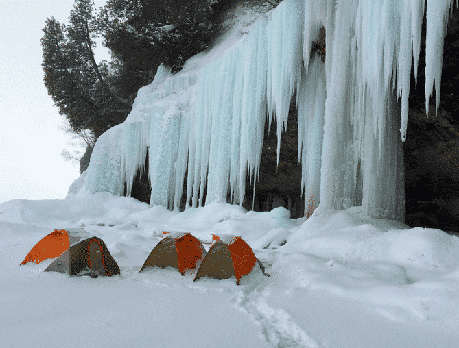 winter camping under frozen waterfall