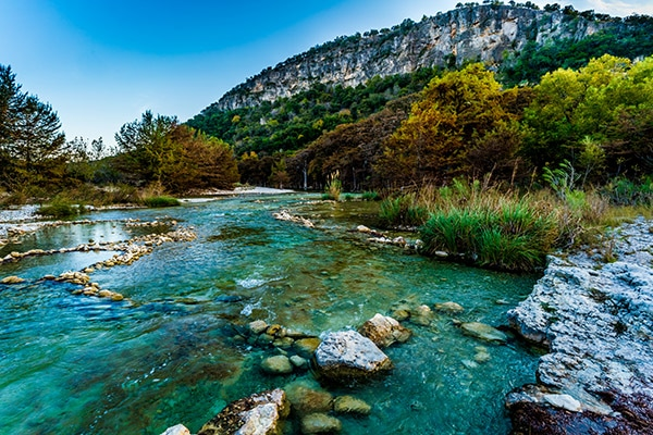 texas camping mountain range view of forest with vibrant blue river running through the center