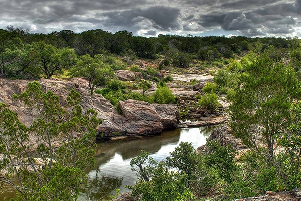 texas camping view of a river running through a brush forest in a desert like landscape with storm clouds in hover over