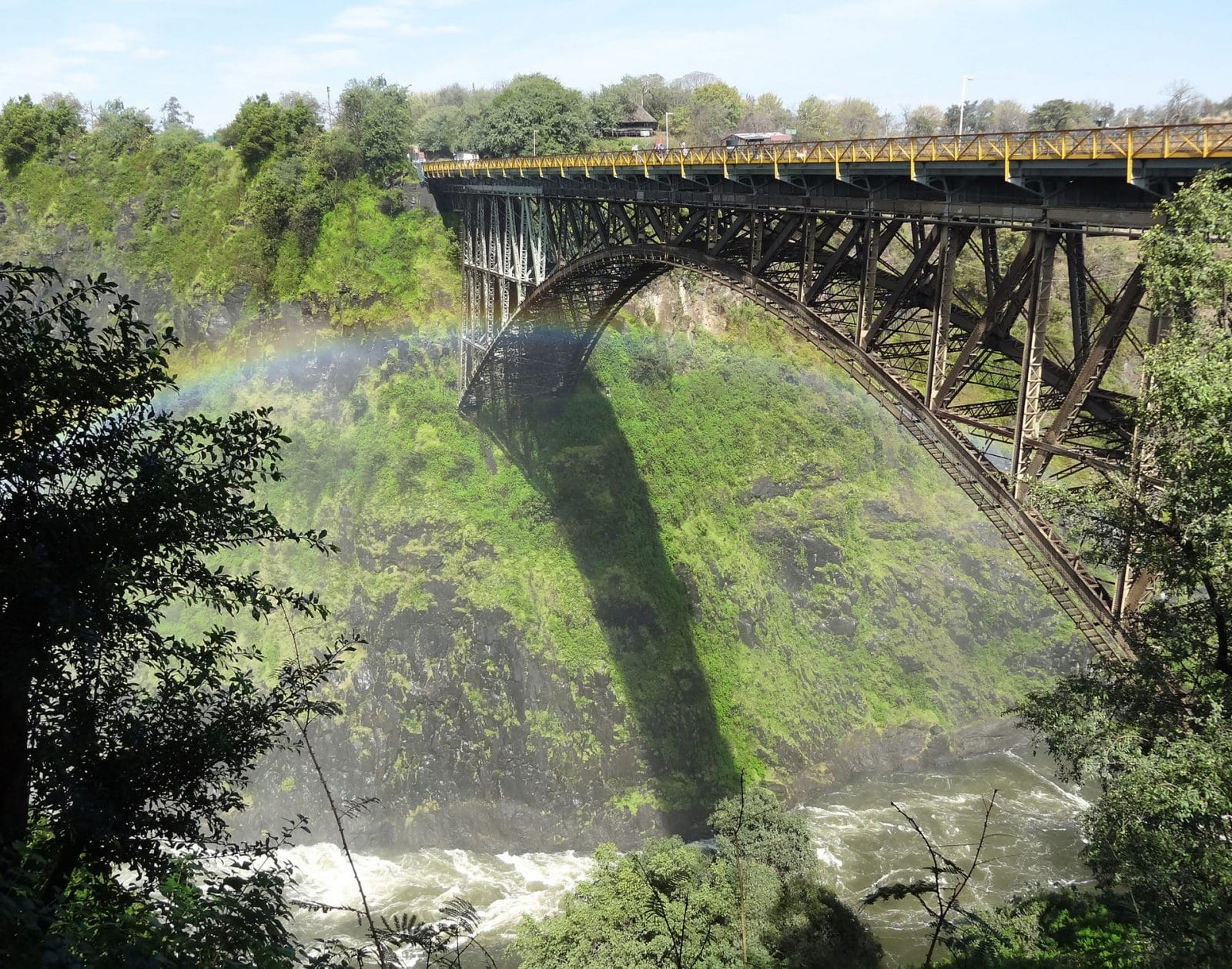 view of a large bridge over a river with rainbow over a small wooded village when boondocking in travel trailer