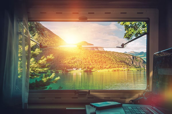 view from inside travel trailer with laptop and sun over looking the ocean and jungle