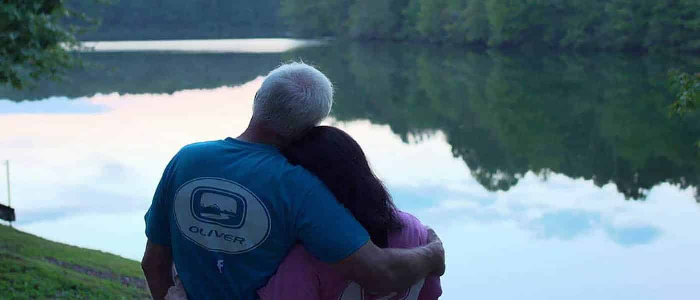 couple enjoy the river view from their oliver travel trailers on delivery day