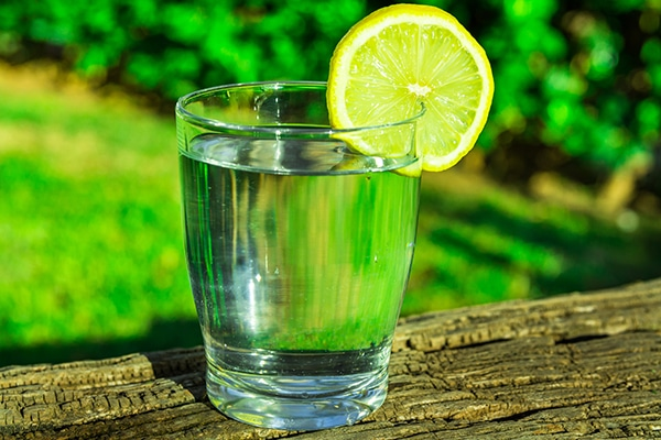 Glass of pure water with lemon wedge circle